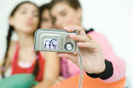 preteen kissing - Three young female friends taking photo of selves with digital camera, focus on camera in foreground Stock Photo - Premium Royalty-Free, Code: 695-05766212