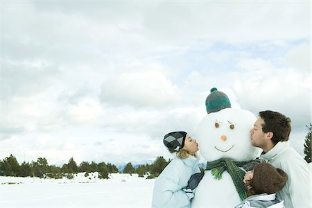 preteen kissing - Three young friends kissing snowman, head and shoulders Stock Photo - Premium Royalty-Free, Code: 695-05766599
