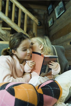 preteen kissing - Preteen girl reading book with toddler, toddler whispering to her Stock Photo - Premium Royalty-Free, Code: 695-05766776