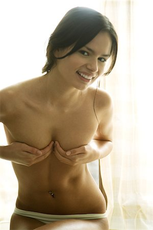 Young woman in underwear covering breasts with hands, smiling at camera Stock Photo - Premium Royalty-Free, Code: 695-05767167