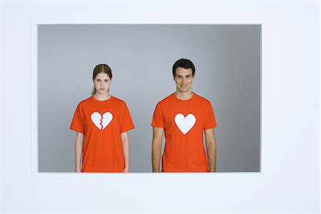 Young couple wearing tee-shirts with heart symbols, woman's heart broken Stock Photo - Premium Royalty-Free, Code: 695-05767877