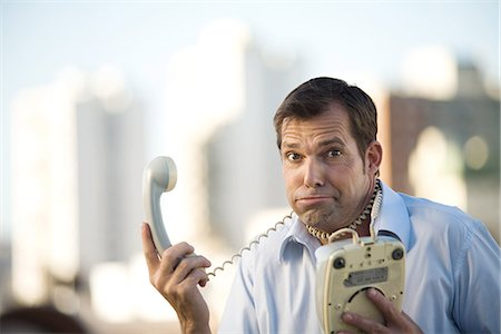 phone cord - Man holding landline phone, cord wrapped around his neck, looking at camera Stock Photo - Premium Royalty-Free, Code: 695-05768175