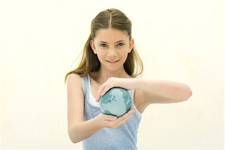 Preteen girl holding small globe in hands, smiling at camera Stock Photo - Premium Royalty-Free, Code: 695-05768225