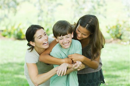 Mother with teenage daughter and son tickling each other Stock Photo - Premium Royalty-Free, Code: 695-05768498