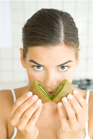 smelly - Woman holding halves of kiwi to her nose, looking at camera Stock Photo - Premium Royalty-Free, Code: 695-05768501