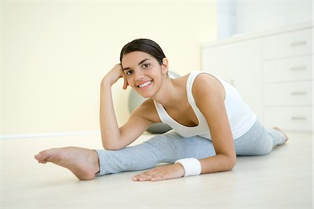 Young woman doing splits, leaning on elbow, smiling at camera Stock Photo - Premium Royalty-Free, Code: 695-05768704