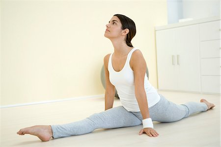 Young woman doing splits, looking up Stock Photo - Premium Royalty-Free, Code: 695-05768703