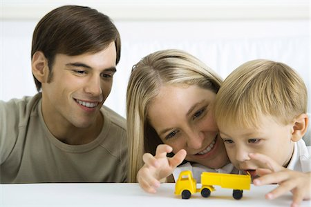 Little boy playing with toy truck, parents watching smiling Stock Photo - Premium Royalty-Free, Code: 695-05768876