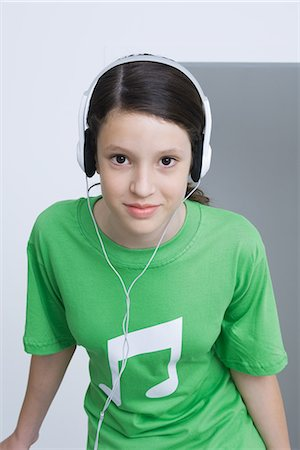 pic music note symbol - Preteen girl wearing tee-shirt printed with musical notes, listening to headphones, smiling Stock Photo - Premium Royalty-Free, Code: 695-05768994