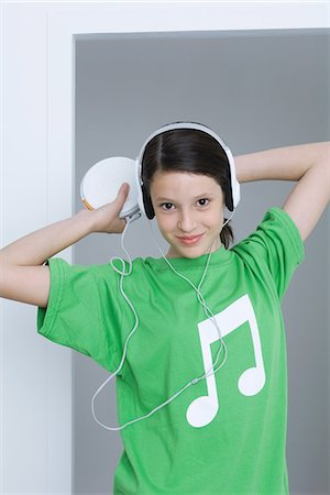 pic music note symbol - Girl listening to portable CD player, wearing tee-shirt with musical note printed on it Stock Photo - Premium Royalty-Free, Code: 695-05768993