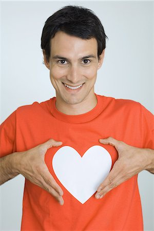 Man holding hands around heart symbol printed on his tee-shirt, smiling at camera Stock Photo - Premium Royalty-Free, Code: 695-05769012