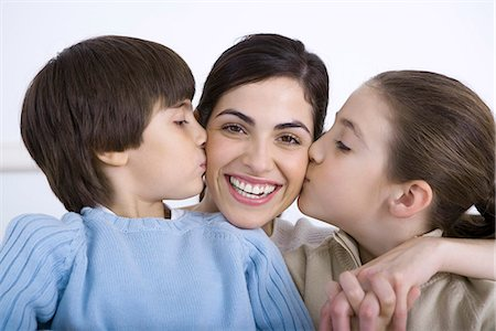 preteen kissing - Portrait of smiling mother being kissed on each cheek by daughter and son Stock Photo - Premium Royalty-Free, Code: 695-05769086