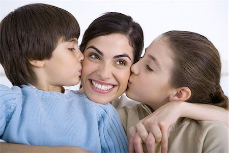 preteen kissing - Portrait of smiling mother being kissed on each cheek by young daughter and son Stock Photo - Premium Royalty-Free, Code: 695-05769087