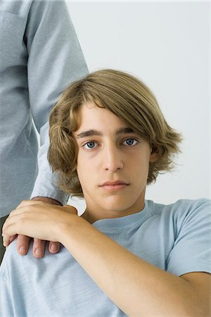 Teen boy holding father's hand on shoulder, looking at camera, cropped view Stock Photo - Premium Royalty-Free, Code: 695-05769195