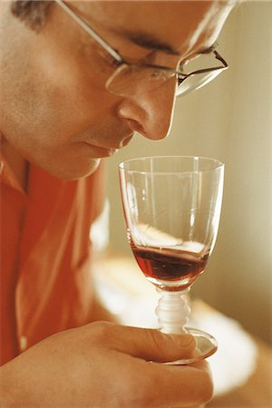 smelly - Man smelling red wine in wine glass Stock Photo - Premium Royalty-Free, Code: 695-05769313