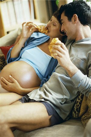 pregnant couple couch - Expecting couple sitting together on sofa, eating croissants Stock Photo - Premium Royalty-Free, Code: 695-05769748