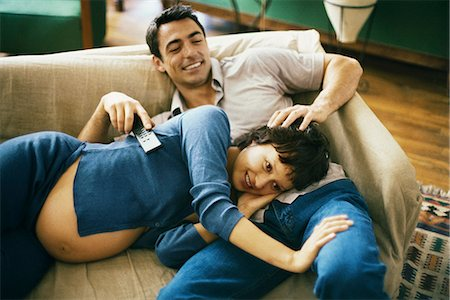 pregnant couple couch - Expecting couple relaxing on sofa, watching TV, woman resting head in man's lap Stock Photo - Premium Royalty-Free, Code: 695-05769765