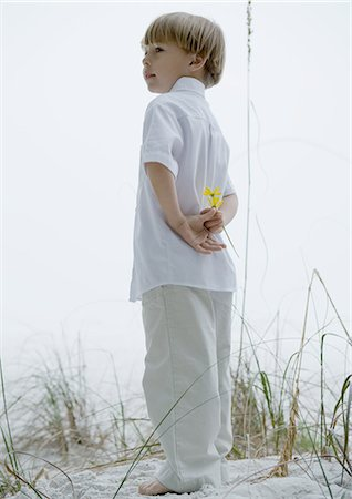 Little boy standing in dunes, holding flowers behind back Stock Photo - Premium Royalty-Free, Code: 695-05762835