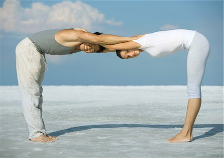 Man and woman bending over, head to head, arms together, on beach Stock Photo - Premium Royalty-Free, Code: 695-05763467