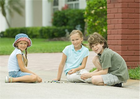 Three children playing marbles outdoors Stock Photo - Premium Royalty-Free, Code: 695-05763531