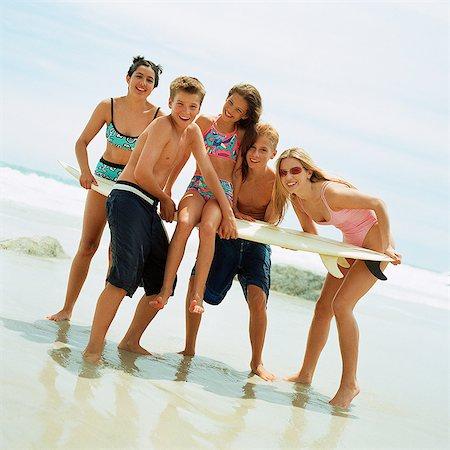 Teenagers on beach holding surfboard Stock Photo - Premium Royalty-Free, Code: 695-05774077