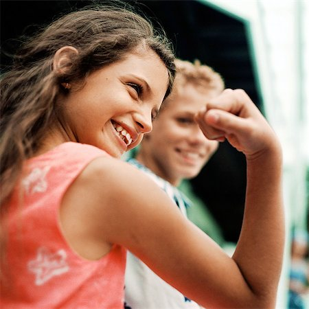 Girl flexing arm muscles, boy in background, smiling Stock Photo - Premium Royalty-Free, Code: 695-05774098