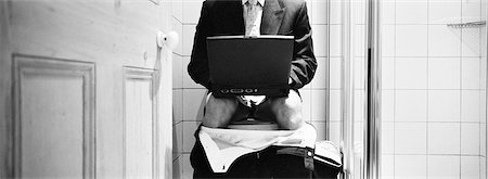 Businessman sitting on toilet with pants down, using laptop, mid-section, b&w, panoramic view Stock Photo - Premium Royalty-Free, Code: 695-05774740