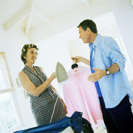 Mature couple facing each other, man holding shirt, woman handing him iron Stock Photo - Premium Royalty-Free, Code: 695-05775108