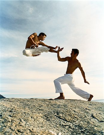 enemy - Two men performing martial arts on rocky ground, one in mid-air, full length Stock Photo - Premium Royalty-Free, Code: 695-05775903