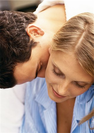 Man leaning over woman's shoulder, kissing woman's neck, close-up Stock Photo - Premium Royalty-Free, Code: 695-05776002