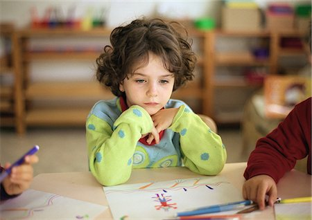 Child sitting at table, head and shoulders Stock Photo - Premium Royalty-Free, Code: 695-05776438