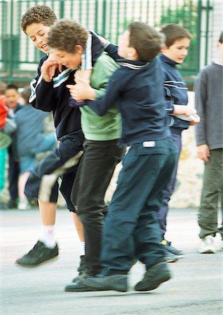 student fighting - Children playfighting in schoolyard Stock Photo - Premium Royalty-Free, Code: 695-05776461