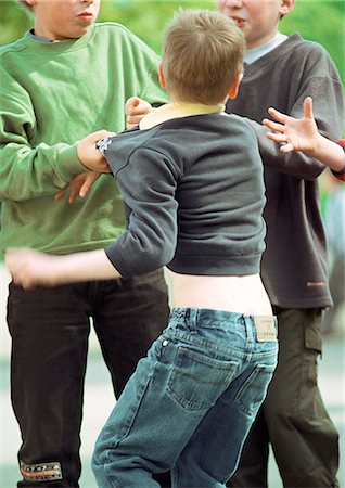 student fighting - Three children fighting, mid-section, rear view, close-up Stock Photo - Premium Royalty-Free, Code: 695-05776462