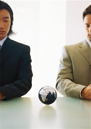 Two businessmen looking down at small globe on table Stock Photo - Premium Royalty-Free, Code: 695-05776897