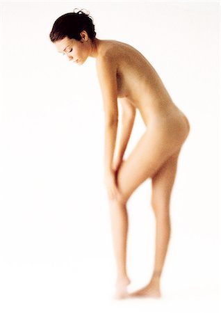 Nude woman standing, bending down, touching knee, side view Stock Photo - Premium Royalty-Free, Code: 695-05777147
