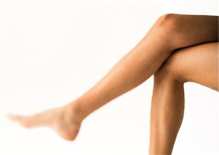 Woman's bare legs, crossed at knee Stock Photo - Premium Royalty-Free, Code: 695-05777148