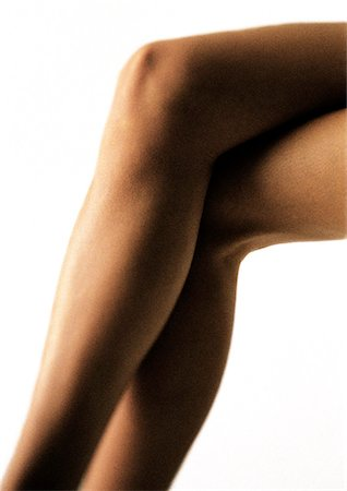 Woman's slender legs crossed at kneed, bare, close up Stock Photo - Premium Royalty-Free, Code: 695-05777161