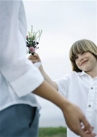Boy handing woman bouquet of wildflowers Stock Photo - Premium Royalty-Free, Code: 695-05777412