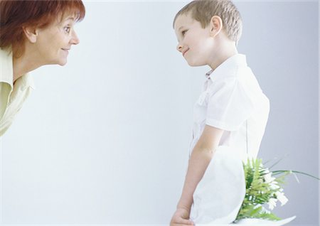 Boy surprising grandmother with bouquet of flowers Stock Photo - Premium Royalty-Free, Code: 695-05777498
