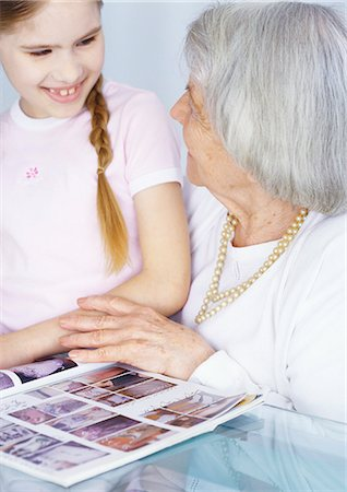 Grandmother and granddaughter looking at magazine together Stock Photo - Premium Royalty-Free, Code: 695-05777500