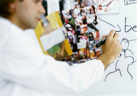 Man writing on board with images taped to it Stock Photo - Premium Royalty-Free, Code: 695-05777802