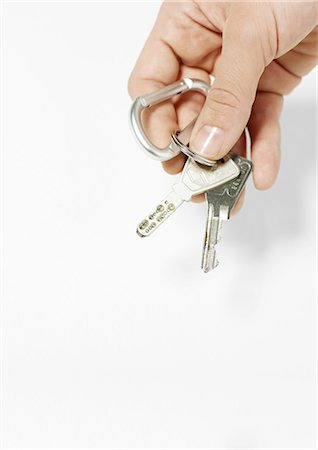 finger holding a key - Hand holding keys Stock Photo - Premium Royalty-Free, Code: 695-05778686