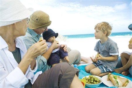 Grandparents and grandchildren having picnic on beach Stock Photo - Premium Royalty-Free, Code: 695-05779168