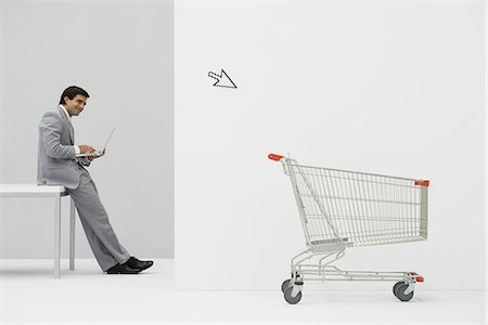 empty shopping cart - Businessman leaning against desk, shopping online, cursor pointing at shopping cart Stock Photo - Premium Royalty-Free, Code: 695-05779420
