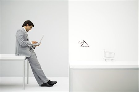 empty shopping cart - Businessman sitting on desk, shopping online, shopping cart and cursor in foreground Stock Photo - Premium Royalty-Free, Code: 695-05779422