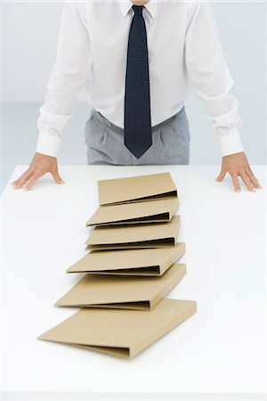 Binders lying on table after a chain reaction of being pushed over, cropped view of businessman Stock Photo - Premium Royalty-Free, Code: 695-05779464