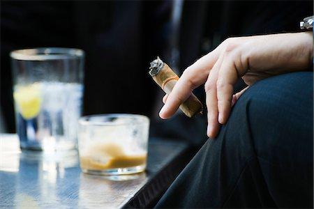Man's hand on knee holding smoking cigar, close-up Stock Photo - Premium Royalty-Free, Code: 695-05779736