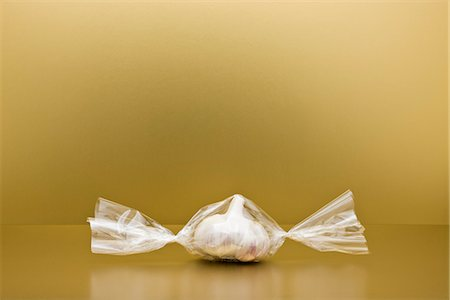 Food concept, head of garlic inside of cellophane candy wrapper Stock Photo - Premium Royalty-Free, Code: 695-05779942