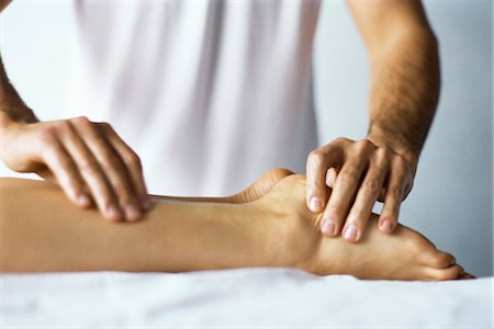 foot massage - Therapist treating patient's foot with acupressure Stock Photo - Premium Royalty-Free, Code: 695-05770248