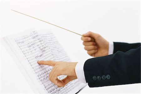 scoring - Conductor's hands with conductor's baton and musical score Stock Photo - Premium Royalty-Free, Code: 695-05770414